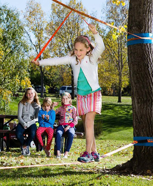 a girl walking on the play line with the help of teaching line, her friends watching