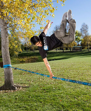 young man doing a stunt on the Trick Line in a park