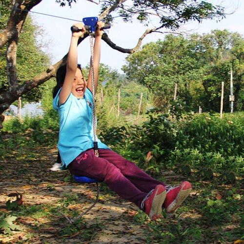 a girl riding on a zipline - Family Backyard Toys Zip Line Review Slackline HiveFly