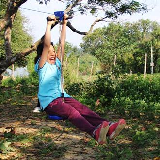 a girl riding on a zipline